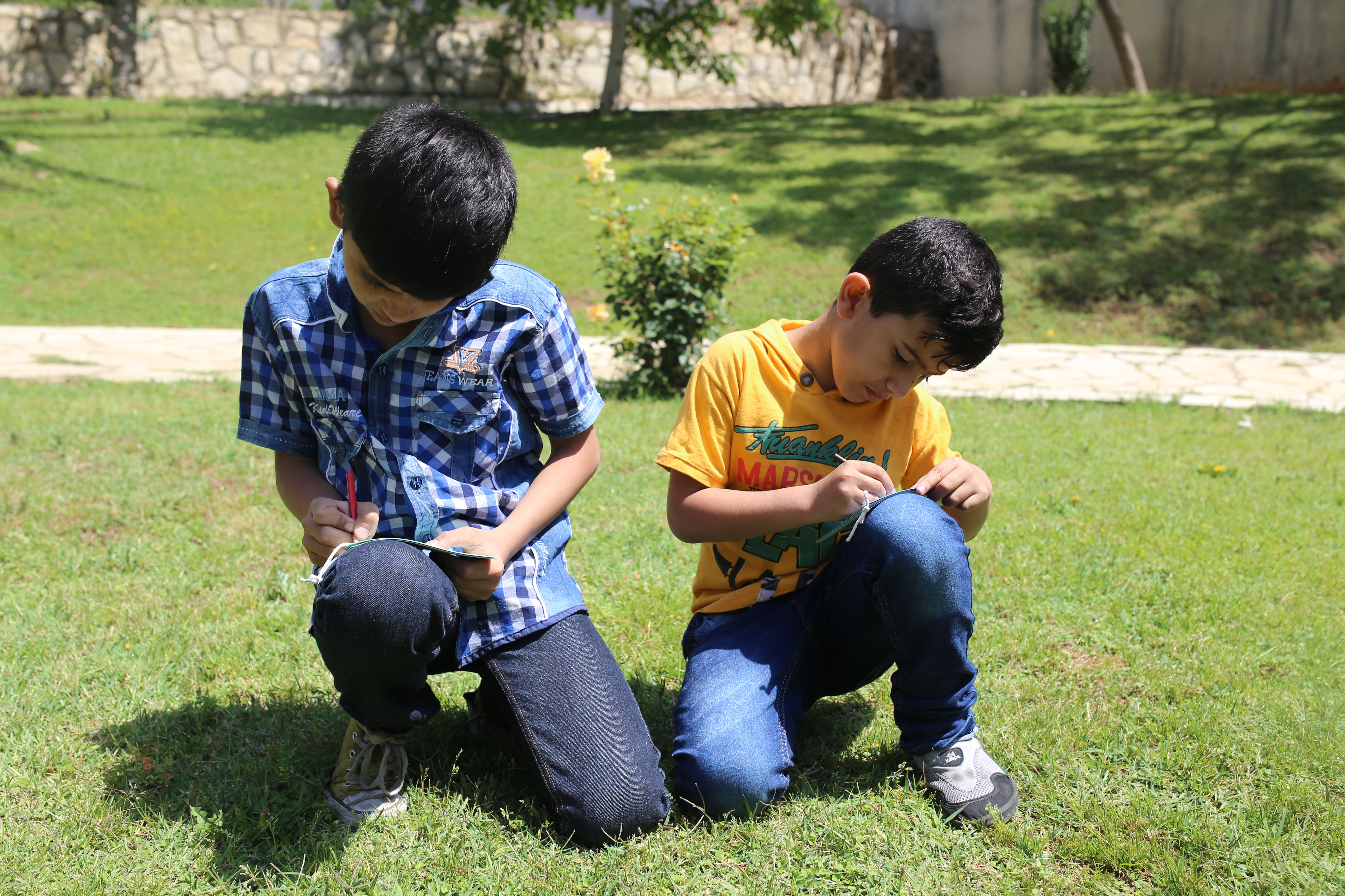teaching with an NGO, working with refugee communities in Lebanon: two boys sit and write outside