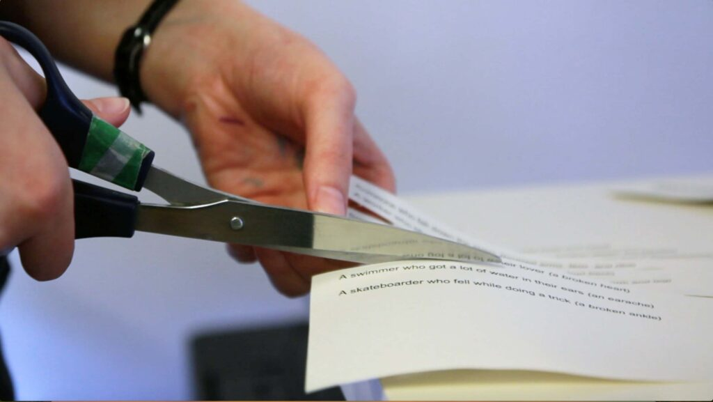 hands cutting with scissors preparing a ESL lesson plan